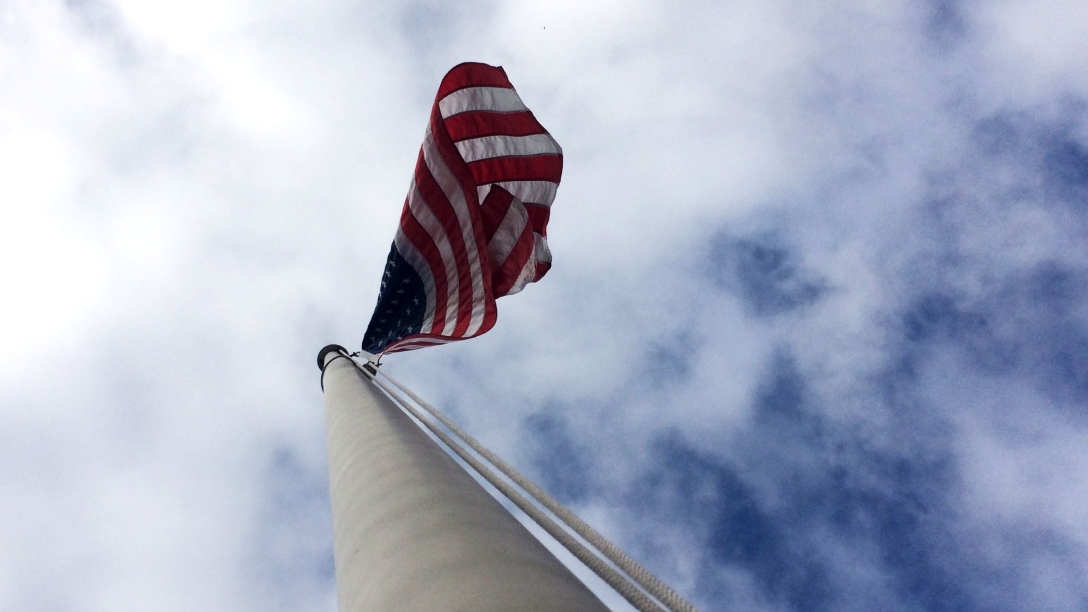 Image of an american flag from below.