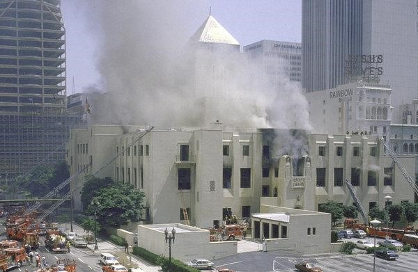 Picture of the LA main library surrounded by firetrucks, smoke billowing.